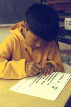 Photograph of a boy communicating by writing.